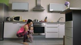 Усмехаясь женщина делая выпады с сыном младенца в руках сток-видео