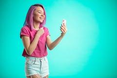 Усмехаясь женщина делая фото selfie на smartphone изолированном на голубой предпосылке Стоковые Фото