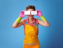 Усмехаясь женщина держа губки кухни перед стороной на сини Стоковое Фото