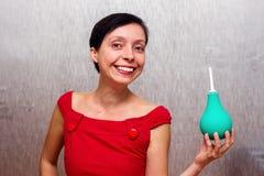 Усмехаясь женщина держа клизму стоковое изображение