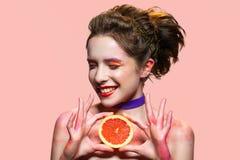 Усмехаясь женщина держа кусок грейпфрута Стоковое Фото