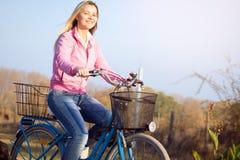 Усмехаясь женщина едет велосипед стоковые изображения rf