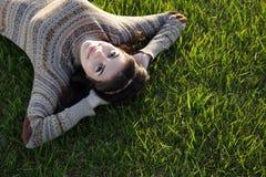Усмехаясь женщина лежа на зеленой траве Стоковые Изображения