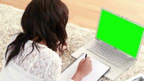 Усмехаясь женщина лежа на поле делая домашнюю работу используя компьтер-книжку сток-видео