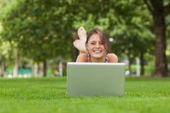 Усмехаясь женщина лежа на траве и использовании компьтер-книжки Стоковая Фотография RF