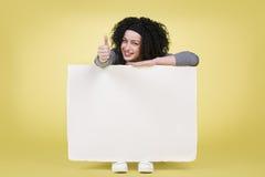 Усмехаясь женщина держа белый знак всходит на борт показывать большие пальцы руки вверх стоковые фотографии rf