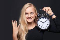 Усмехаясь женщина держа будильник и подсчитывать стоковые фотографии rf