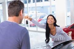 Усмехаясь женщина держа ее новый ключ Стоковые Изображения