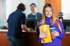 Усмехаясь женщина держа закуски пока приобретение человека стоковые фото