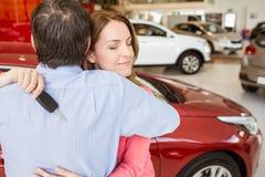Усмехаясь женщина держа ключ пока обнимающ ее супруга Стоковое фото RF