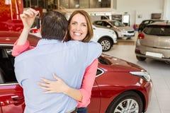 Усмехаясь женщина держа ключ пока обнимающ ее супруга Стоковая Фотография