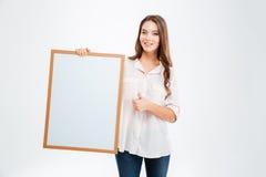 Усмехаясь женщина держа пустую доску и показывая большой палец руки вверх Стоковое Изображение