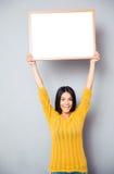 Усмехаясь женщина держа пустую доску Стоковые Изображения