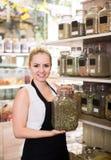 Усмехаясь женщина держа стекло может с травами Стоковое фото RF
