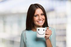 Усмехаясь женщина держа усмехаясь чашку стоковые изображения rf