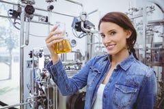 Усмехаясь женщина держа beaker пива Стоковые Фотографии RF