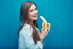 Усмехаясь женщина есть банан background card congratulation invitation Стоковые Фотографии RF