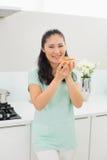 Усмехаясь женщина есть кусок пиццы в кухне Стоковое Фото
