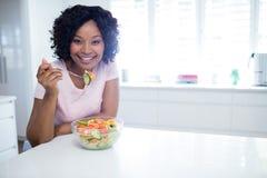 Усмехаясь женщина есть салат в кухне Стоковая Фотография RF