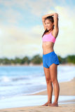 Усмехаясь женщина делая протягивающ тренировку на пляже стоковая фотография rf