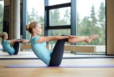 Усмехаясь женщина делая тренировки на циновке в спортзале стоковая фотография
