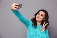 Усмехаясь женщина делая фото selfie на smartphone Стоковые Изображения