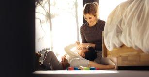 Усмехаясь женщина играя с мальчиком стоковая фотография