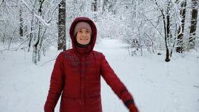 Усмехаясь женщина идя в лес покрытый снегом, наслаждаясь природой зимы, ослабляет акции видеоматериалы