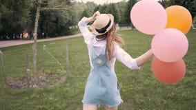 Усмехаясь женщина имбиря в солнечных очках бежать и завихряясь с воздушными шарами в парке сток-видео
