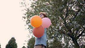 Усмехаясь женщина имбиря в солнечных очках стоя с воздушными шарами в парке лета видеоматериал