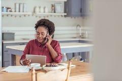 Усмехаясь женщина используя таблетку и говорящ на телефоне стоковая фотография