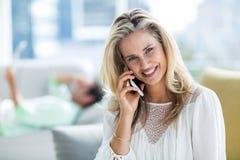 Усмехаясь женщина используя мобильный телефон дома стоковое фото