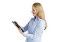 Усмехаясь женщина используя таблетку сенсорного экрана Стоковое фото RF