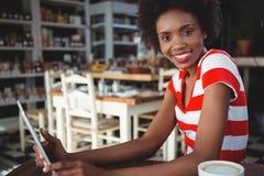 Усмехаясь женщина используя цифровую таблетку в кафе Стоковые Фото
