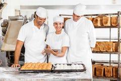 Усмехаясь женщина используя цифров с коллегами в хлебопекарне Стоковые Фото
