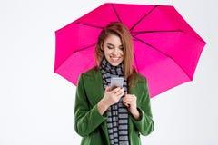 Усмехаясь женщина используя smartphone под зонтиком Стоковые Изображения