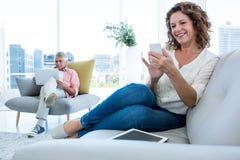 Усмехаясь женщина используя smartphone человеком сидя дома Стоковое Фото