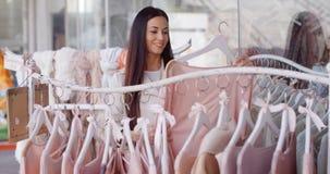 Усмехаясь женщина ища для одежд Стоковое Фото