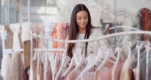 Усмехаясь женщина ища для одежд Стоковое фото RF
