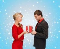 Усмехаясь женщина и человек с подарочной коробкой Стоковая Фотография