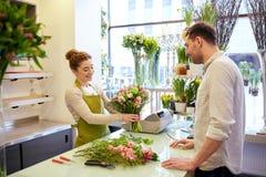 Усмехаясь женщина и человек флориста на цветочном магазине стоковое фото rf