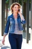 Усмехаясь женщина идя в город говоря на мобильном телефоне Стоковое Изображение