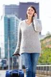 Усмехаясь женщина идя и говоря на мобильном телефоне с чемоданом Стоковые Фотографии RF