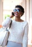 Усмехаясь женщина идя и говоря на мобильном телефоне Стоковое Изображение RF