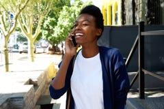 Усмехаясь женщина идя и говоря на мобильном телефоне Стоковая Фотография RF
