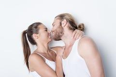 Усмехаясь женщина идя расцеловать супруга изолированного на белизне Стоковое Изображение