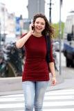 Усмехаясь женщина идя outdoors и говоря на мобильном телефоне Стоковое Изображение