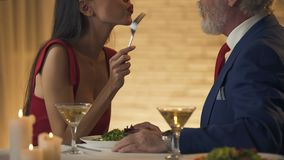 Усмехаясь женщина кормить ее старый парня в ресторане, датировка, паре в любов видеоматериал