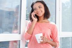 Усмехаясь женщина мулата говоря в сотовый телефон Стоковая Фотография RF