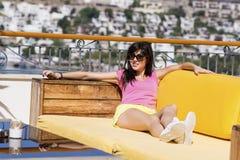 усмехаясь женщина наслаждаясь летними каникулами лежа на sunbed в баре моря стоковые фото